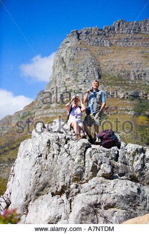 Reife Wanderer ruht auf Felsen in Bergen Frau Blick auf Landschaft durch Fernglas Mann mit Becher - Stockfoto