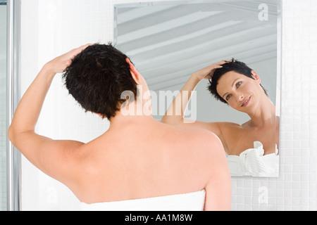 Frau im Spiegel betrachtet - Stockfoto