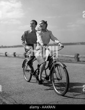 1950ER JAHREN LÄCHELN GLÜCKLICHES PAAR MANN FRAU TANDEM FAHRRAD FÜR ZWEI GEBAUT - Stockfoto
