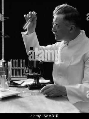1920ER-1930ER JAHREN 1940ER JAHREN WISSENSCHAFTLER LABORANTIN IM WEIßEN KITTEL LOOKING AT REAGENZGLAS VOR MIKROSKOP - Stockfoto