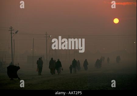 KUMBH MELA INDIEN 2001 AS THE SUN SETS DER RAUCH VOM FEUER MACHT EINEN DICKEN SMOG PILGER ZURÜCK ZU IHREN CAMPS - Stockfoto