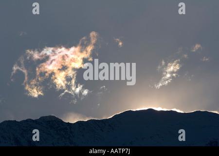 Licht reflektiert in den Wolken und hohe Winde wehenden Schnee von den Bergrücken oberhalb Val Venosta, Südtirol, - Stockfoto
