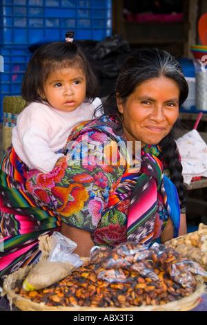 Bunte Frau mit Enkelin auf Rückseite im Markt in touristischen Dorf von Antigua Guatemala - Stockfoto