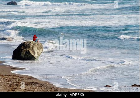 Ozean beobachten. Ein junger Mann sitzt auf einem Stein an den Pazifischen Ozean in Carpinteria, Kalifornien - Stockfoto