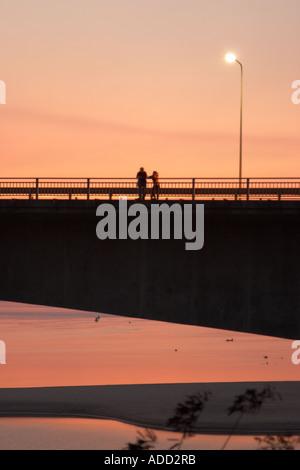 Zwei Menschen stehen auf Lao japanische Brücke über den Mekong Fluss bei Sonnenuntergang - Stockfoto