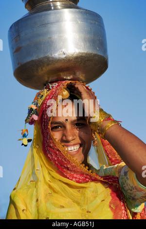 Frau Wassertragen auf traditionelle Weise aus einem Brunnen außerhalb Pushkar Indien Modell veröffentlicht - Stockfoto