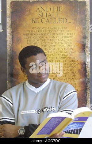 Männliche schwarze Student an der Arbeit studieren aus Lehrbuch vor der religiösen Plakat - Stockfoto