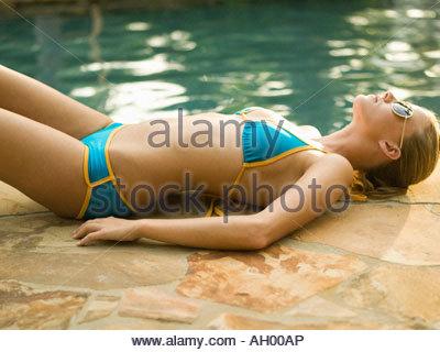 Teenager-Mädchen im Bikini Sonnen neben Schwimmbad - Stockfoto