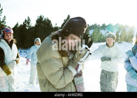 Junge Freunde werfen Schneebälle, lächelnd, verschwommen Bewegung - Stockfoto