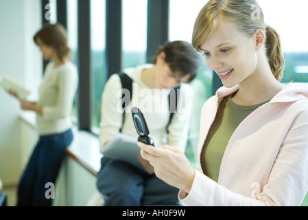 Studentin Blick auf Handy vor Fenster, lächelnd, Studenten im Hintergrund - Stockfoto