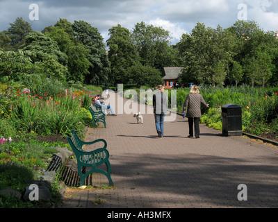 Menschen zu Fuß einen Hund im Kelvingrove Park, Glasgow. - Stockfoto