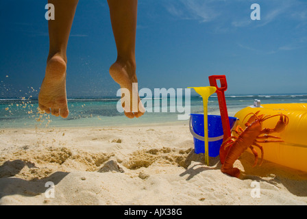 Mädchen springen vor Freude an tropischen weißen Sandstrand mit Strandspielzeug im Vordergrund blauen Himmel und - Stockfoto