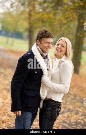 Verspieltes paar in Autumn leaves - Stockfoto