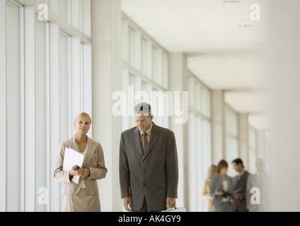 Führungskräfte zu Fuß durch den Korridor des Bürogebäudes - Stockfoto