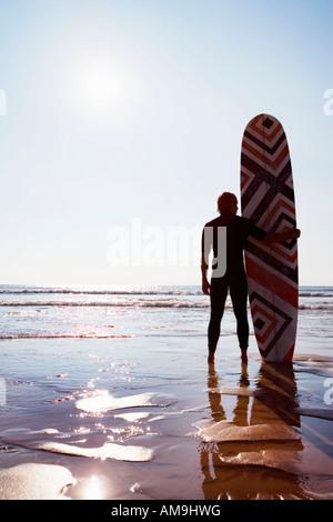 Mann mit Surfbrett am Strand. - Stockfoto