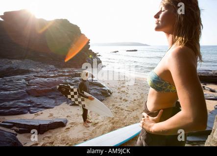 Paar steht am Strand mit Surfbrettern. - Stockfoto