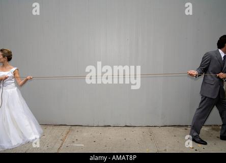 Eine Braut und Bräutigam ziehen ein Seil in verschiedene Richtungen - Stockfoto