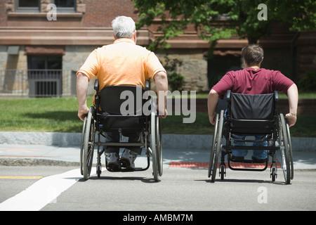 Rückansicht des ein Mann mittleren Alters und eine Frau mittleren Alters, die beim Überqueren einer Straße im Rollstuhl - Stockfoto