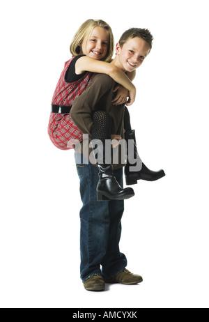 Jungen und Mädchen Huckepack Reiten lächelnd - Stockfoto