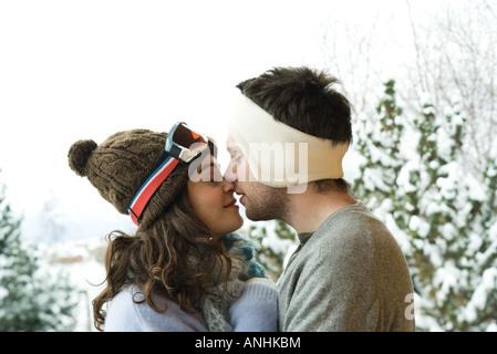 Junges Paar in Winterkleidung, küssen, Seitenansicht - Stockfoto