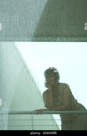 Frau, die durch Fenster in Regen - Stockfoto