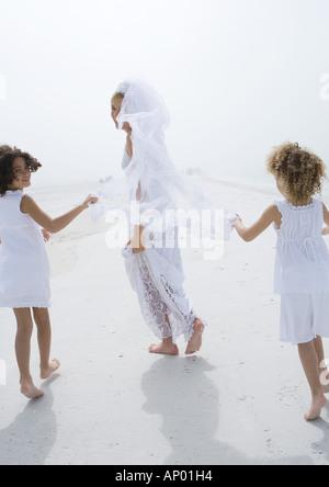 Braut und Blume Mädchen läuft am Strand - Stockfoto