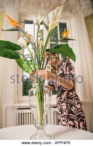 Junge Frau, die Vermittlung von Blumen in einer vase - Stockfoto