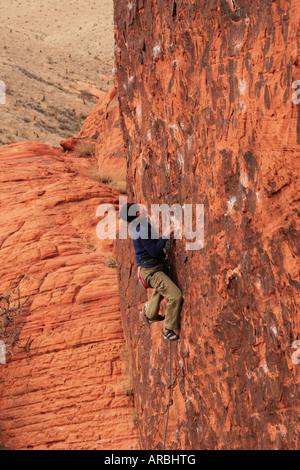 Asiatische Frau Vorsteiger klettert eine vertikale rote Sandstein-Felswand - Stockfoto