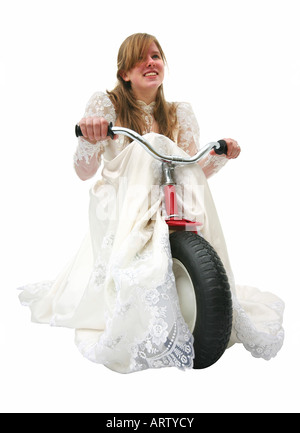 Eine junge Braut im Brautkleid, ein Dreirad fahren, ziehen den Zug hinter ihr. - Stockfoto