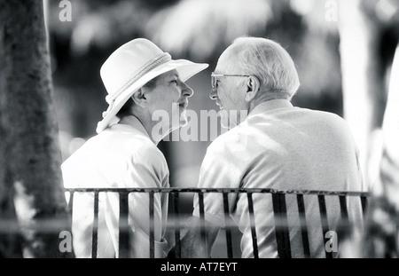 Ein älteres Paar eng auf einer Parkbank im Gespräch - Stockfoto