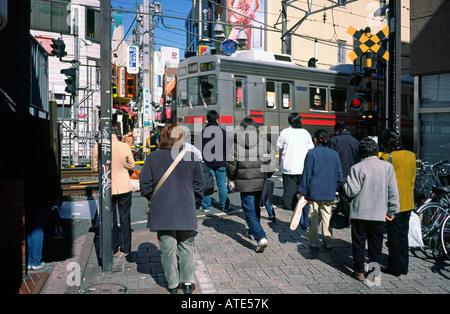 Einheimischen warten an einer automatischen Bahnübergang in Tokios Jiyugaoka für rapid express Zug übergeben. - Stockfoto