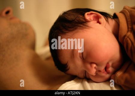 Babymädchen schlafend an des Vaters Brust - Stockfoto