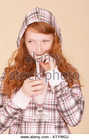 Junges Mädchen im Haus trinken Erdbeer Milchshake - Stockfoto