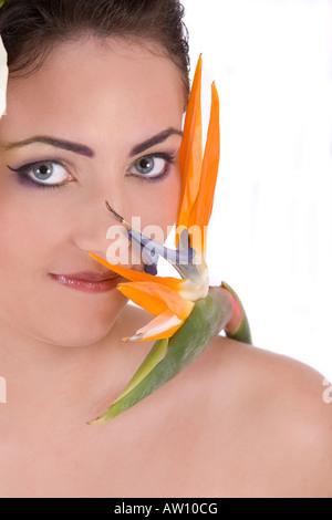 Schöne Brünette mit tropischen Paradiesvogel Blume - Stockfoto