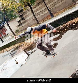 Junger Mann in der Luft auf skateboard - Stockfoto