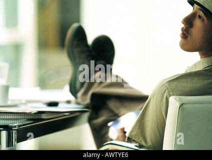 Mann sitzt im Stuhl mit den Füßen auf dem Tisch, Blick auf die Seite, hintere Ansicht - Stockfoto