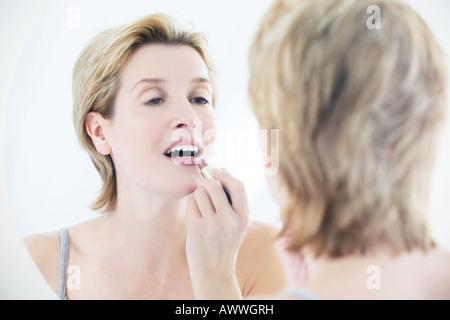 Eine Frau Auftragen von Lippenstift im Spiegel - Stockfoto