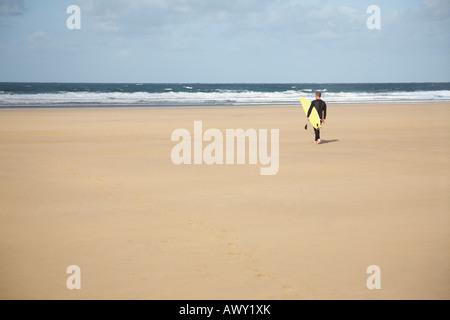 Surfer mit Surfbrett zu Fuß am Strand, Rückansicht - Stockfoto