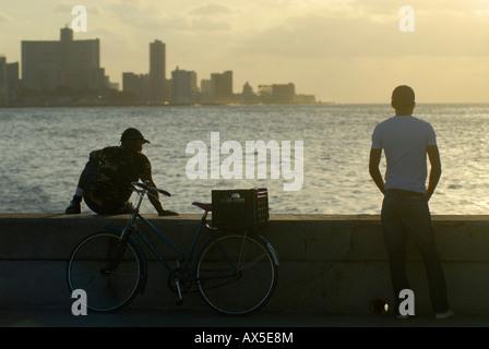 Zwei Männer und ein Fahrrad auf dem Malecón, Sonnenuntergang, Havanna, Kuba - Stockfoto