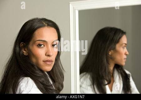 Hübsche junge Frau, die neben einem Spiegel Stand und wir können ihr Spiegelbild sehen. Sie schaut ruhig oder ernst. - Stockfoto