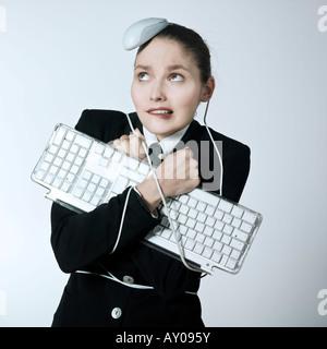 Studio gedreht Porträt einer schönen jungen Frau in einem Kostüm Anzug an eine Computer-Tastatur und wurde Angriff - Stockfoto