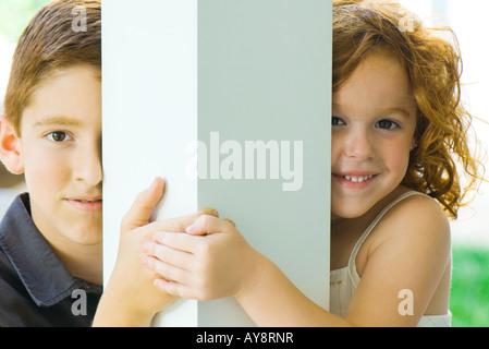 Bruder und Schwester spähen um Spalte in die Kamera, Hand in Hand, Lächeln - Stockfoto