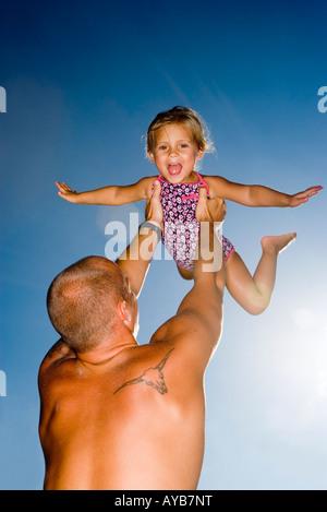 Junger Vater Holding Tochter oben in der Luft - Stockfoto