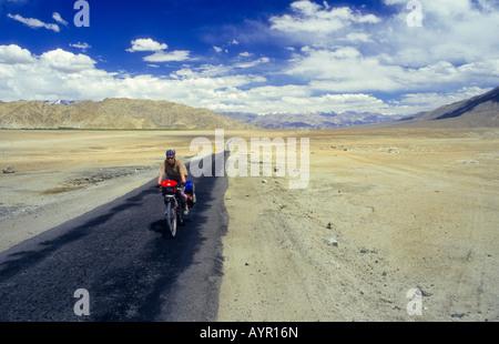 Radfahrer tragen Kopfbedeckung mit voll beladenen Fahrrad auf einer einsamen Strecke von Wüste, Ladakh, Indien - Stockfoto