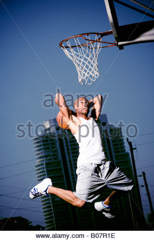 Young African American Mann springt mit einem Basketball auf einem städtischen Basketballplatz - Stockfoto