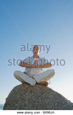 Reifer Mann sitzt auf Felsen Yoga Übung mit blauen Himmel im Hintergrund - Stockfoto