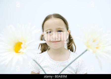 Kleines Mädchen lächelnd in die Kamera, großen Blüten im Vordergrund, Porträt - Stockfoto