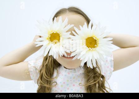 Kleines Mädchen hält Gerbera Gänseblümchen vor Augen, Lächeln, Porträt - Stockfoto