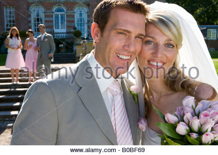 Braut und Bräutigam lächelnd, Brautjungfer und Usher im Hintergrund, Porträt, Nahaufnahme - Stockfoto