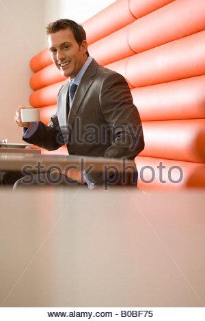 Geschäftsmann mit Tasse am Tisch stand, Lächeln, Porträt, niedrigen Winkel Ansicht - Stockfoto